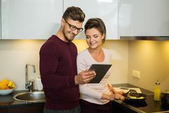 Family reading recipe in a kitchen Stock Photo