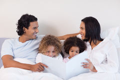 Family reading a story in the bedroom Stock Image