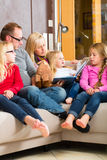 Family reading story in book on sofa in home. Family sitting together with mother, father and children comfortable on sofa, listening to fairy tale from story Royalty Free Stock Photo