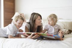 Family Reading Storybook In Bed Stock Photos