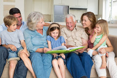 Family reading storybook in living room Royalty Free Stock Photo