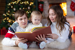 Family reading together on Christmas evening Royalty Free Stock Photos