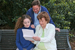 Family Reading Together Horizontal. A father, daughter and grandmother reading together in the park.  Horizontal orientation Stock Images