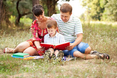 Family reading together. Summer holiday. Happy father, mother and son reading book on the lawn in the park. Family reading together. Summer holiday. Happy family Royalty Free Stock Image