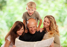 Family reads newspaper. Family reads the newspaper outdoors Stock Image