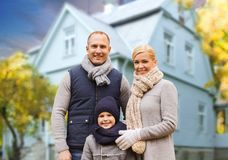 Happy family over living house in autumn stock image