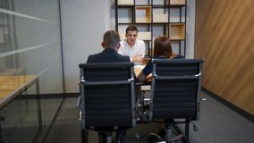 Family with realtor in boardroom discussing about mortgage contract. Redhair female and her husband very interested in signing documetns in businesscenter stock footage