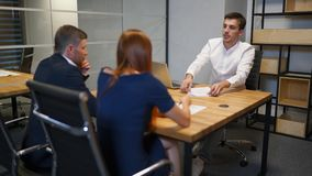 Family and realtor businessman in boardroom discussing about mortgage contract. Wife in blue dress and her husband in formal suit very interested in signing stock footage