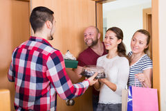 Family receiving visitors. Family couple receiving visitors with the gifts in the home Royalty Free Stock Photos