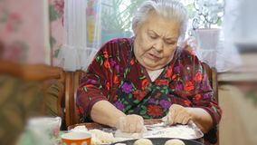 A family recipe, grandma`s hands knead the dough for buns stock footage