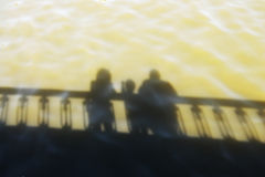 Family reflection. Reflection in the water of the family standing on the bridge Stock Image