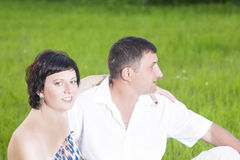Family Relationships Concepts. Portrait of Caucasian Couple Rela. Xing Together Outdoors on Grass in Park. Sitting Embraced. Horizontal Shot Stock Image