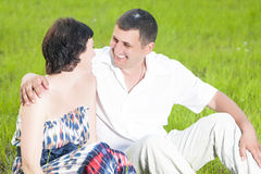 Family Relationships. Happy Caucasian Couple Relaxing Together. Outdoors on Grass in Park. Sitting Embraced and Looking at Each Other. Smiling. Horizontal Shot Stock Image