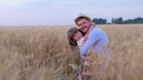 Family relationships, happy man cheerfully hugs little joyful girl and smile on field with ripe wheat during mature