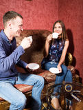 Family relationships, a young couple sitting on a sofa and drink tea, they are smiling and happy Stock Photography