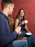 Family relationships, a young couple sitting on a sofa and drink tea, they are smiling and happy Stock Image