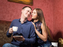 Family relationships, a young couple sitting on a sofa and drink tea, they are smiling and happy Royalty Free Stock Photos