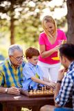 Family relax in nature and playing chess stock photography