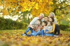 Family relaxing in autumn park. Happy smiling family relaxing in autumn park Royalty Free Stock Photography