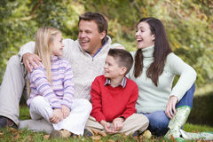 Family relaxing in autumn woodlands Stock Image