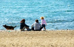 Family relaxing on beach Stock Images