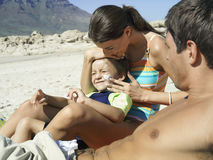 Family relaxing on beach, boy (4-6) sitting in mother's lap, woman applying suncream to son's face, side view Stock Images