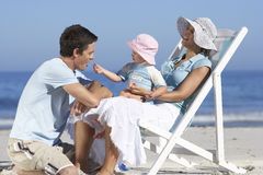 Family relaxing on beach, girl (2-4) on mother's lap in deckchair, wearing sun hats, side view Royalty Free Stock Photo