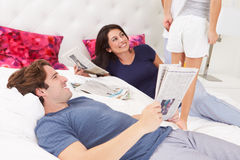 Family Relaxing In Bed With Coffee And Newspaper Royalty Free Stock Photos