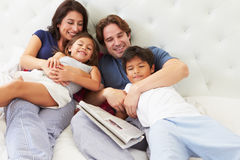 Family Relaxing In Bed With Coffee And Newspaper Stock Photo