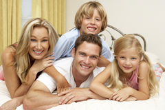 Family Relaxing On Bed At Home Stock Photo
