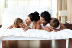 Family relaxing on the bed together Stock Photos