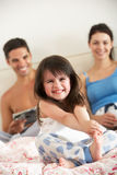 Family Relaxing In Bed Together stock images