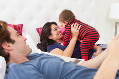 Family Relaxing In Bed With Young Son stock photography