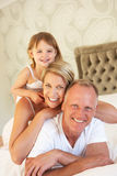 Family Relaxing In Bedroom Stock Photography