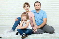 Family relaxing on floor at home. The family father, mother and happy daughter sitting on floor hugging and looking at Royalty Free Stock Photography