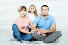 Family relaxing on floor at home. The family father, mother and happy daughter sitting on floor hugging and looking at Stock Photos