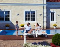 Family relaxing in front of modern house with pool Royalty Free Stock Photo