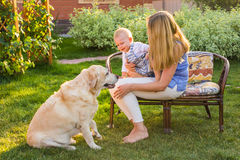 Family Relaxing In Garden With Pet Dog.  royalty free stock photos