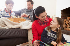 Family Relaxing Indoors Playing Chess And Reading Book Royalty Free Stock Photos