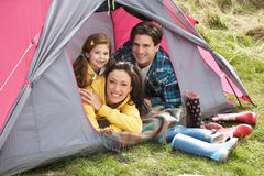Family Relaxing Inside Tent On Camping Holiday. Young Family Relaxing Inside Tent On Camping Holiday stock photography