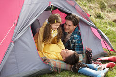 Family Relaxing Inside Tent On Camping Holiday Royalty Free Stock Image