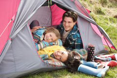 Family Relaxing Inside Tent On Camping Holiday royalty free stock images