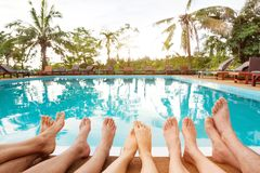 Family relaxing near swimming pool in hotel, feet of group of friends. Or parents with children, happy beach holidays Stock Photos