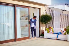 Family relaxing outdoor on rooftop patio with open space kitchen and sliding doors Royalty Free Stock Photo