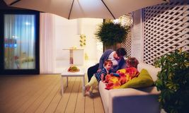 Family relaxing on patio zone with open space kitchen and sliding doors on background. Family relaxing at patio area with open space kitchen and sliding doors on royalty free stock photos