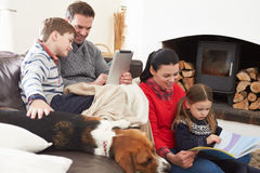 Family Relaxing Reading Book And Using Digital Tablet Royalty Free Stock Photos