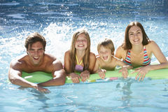 Family Relaxing In Swimming Pool Together Stock Photography