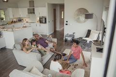 Enjoying Board Games on Hoilday. Family relaxing in their holiday home. Two of the children are playing chess while the rest of the family watch Royalty Free Stock Images