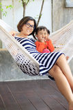 Family relaxing time mother and young kid on white clothes cradl Stock Images