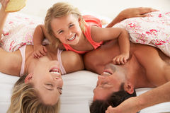 Family Relaxing Together In Bed Stock Images